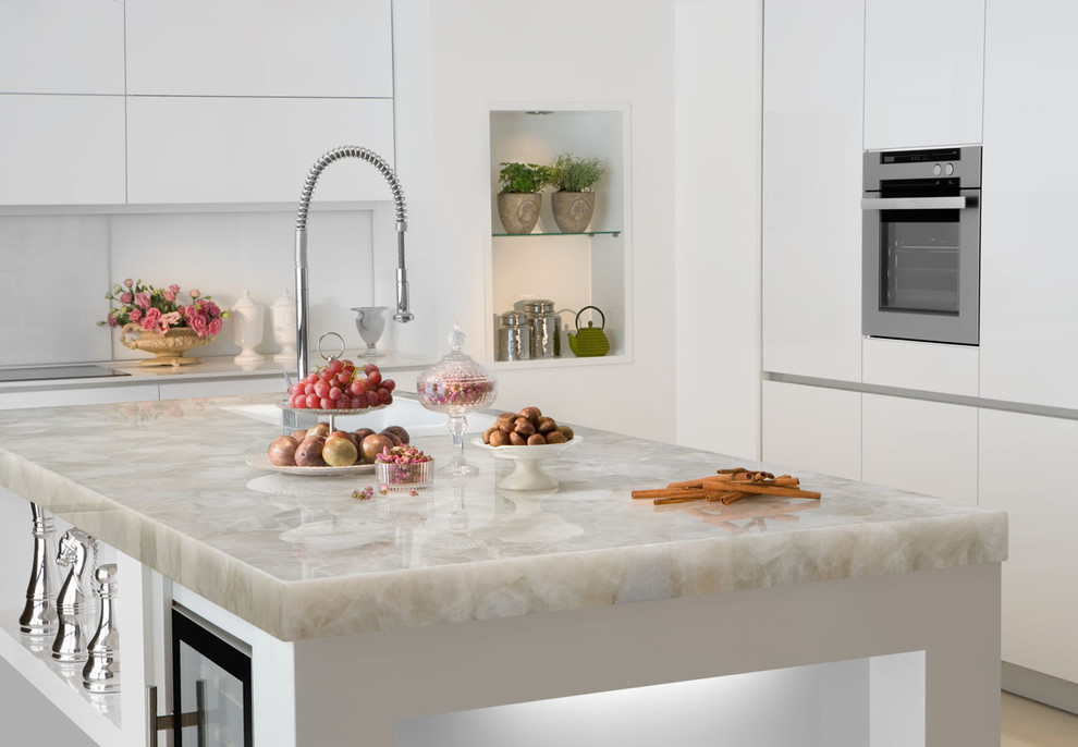 Example of a large trendy u-shaped beige floor enclosed kitchen design in Miami with a double-bowl sink, flat-panel cabinets, white cabinets, quartzite countertops, white backsplash, stainless steel appliances and an island