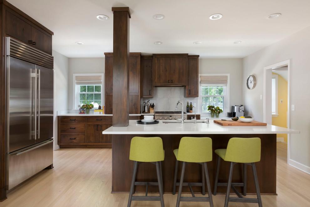 Large transitional u-shaped light wood floor kitchen photo in Milwaukee with an undermount sink, flat-panel cabinets, dark wood cabinets, quartz countertops, white backsplash, ceramic backsplash, stainless steel appliances and an island