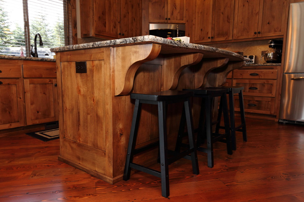 Eat-in kitchen - large rustic l-shaped dark wood floor eat-in kitchen idea in Portland with an undermount sink, medium tone wood cabinets, granite countertops, multicolored backsplash, stone tile backsplash, stainless steel appliances and an island