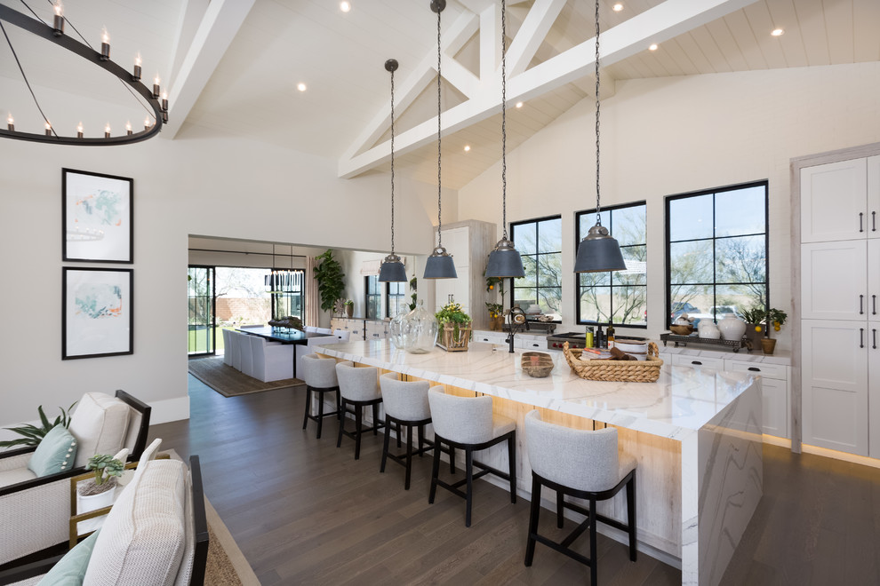 Large trendy galley dark wood floor and brown floor open concept kitchen photo in Phoenix with shaker cabinets, white cabinets, an island, white countertops, an undermount sink, quartz countertops and paneled appliances