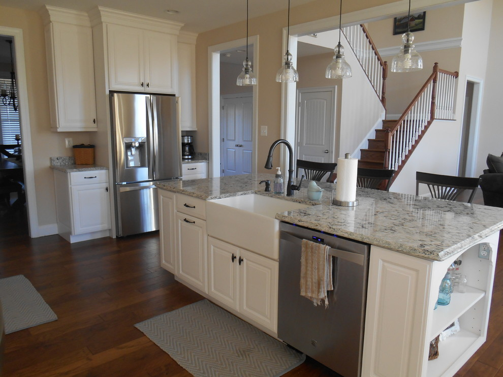 Large transitional u-shaped medium tone wood floor and brown floor open concept kitchen photo in Baltimore with raised-panel cabinets, white cabinets, granite countertops, stainless steel appliances, an island and a farmhouse sink