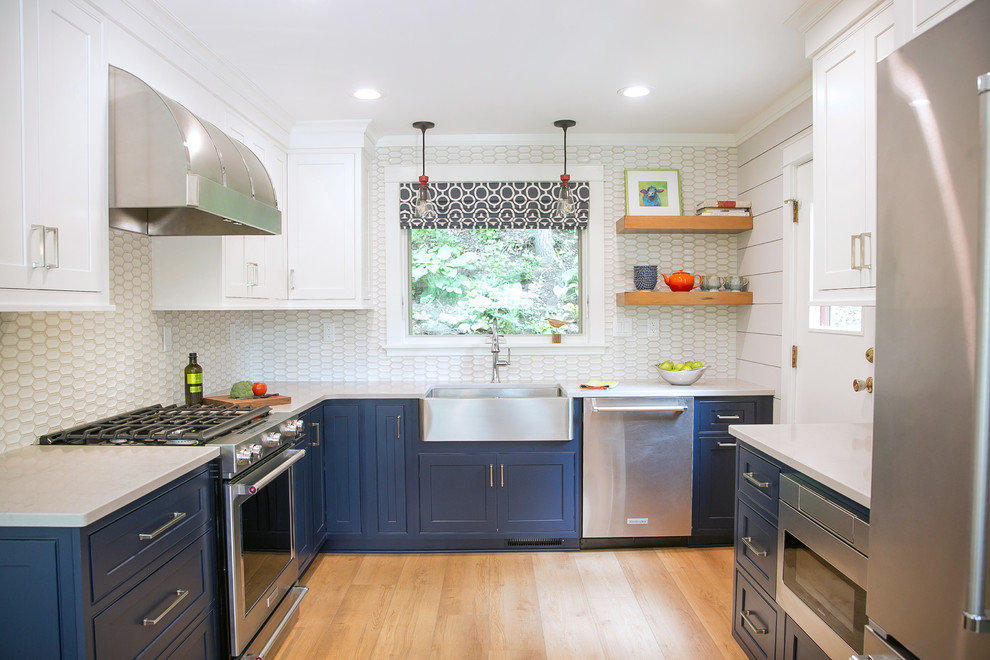 Inspiration for a small coastal u-shaped light wood floor and beige floor enclosed kitchen remodel in Milwaukee with a farmhouse sink, recessed-panel cabinets, blue cabinets, quartz countertops, white backsplash, porcelain backsplash, stainless steel appliances and beige countertops