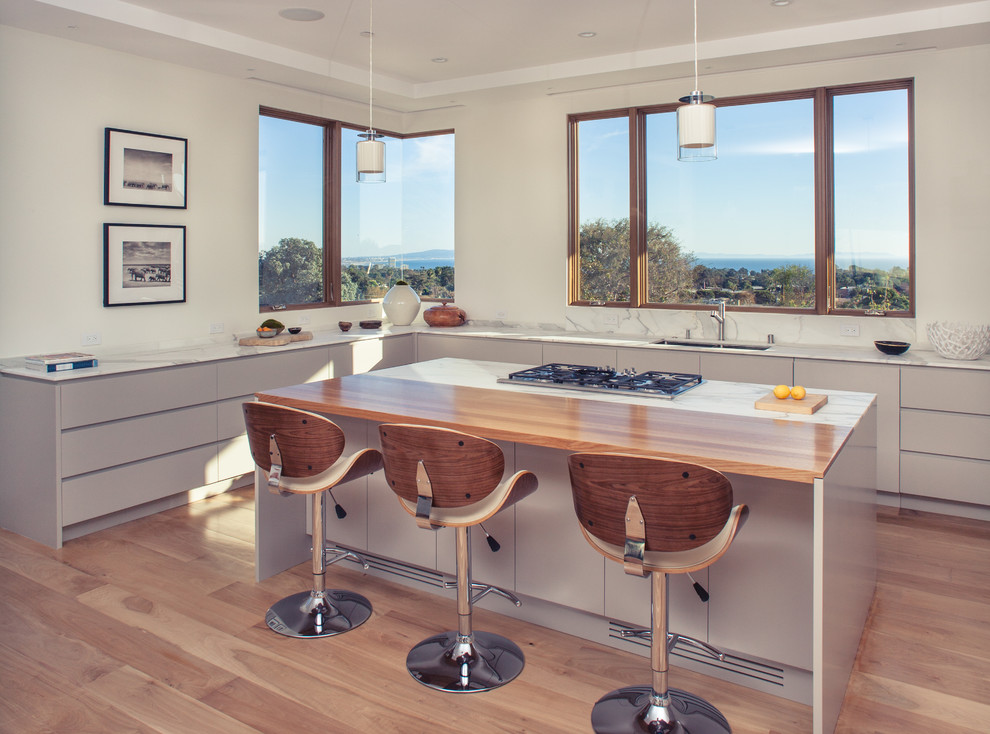 Open concept kitchen - large contemporary u-shaped medium tone wood floor open concept kitchen idea in Los Angeles with an undermount sink, recessed-panel cabinets, gray cabinets, marble countertops, white backsplash, stone slab backsplash, stainless steel appliances and an island