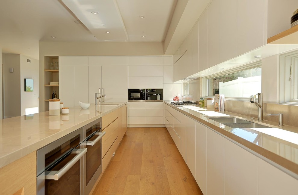 Eat-in kitchen - large modern l-shaped medium tone wood floor eat-in kitchen idea in Los Angeles with an undermount sink, flat-panel cabinets, white cabinets, marble countertops, gray backsplash, stone slab backsplash, stainless steel appliances and an island