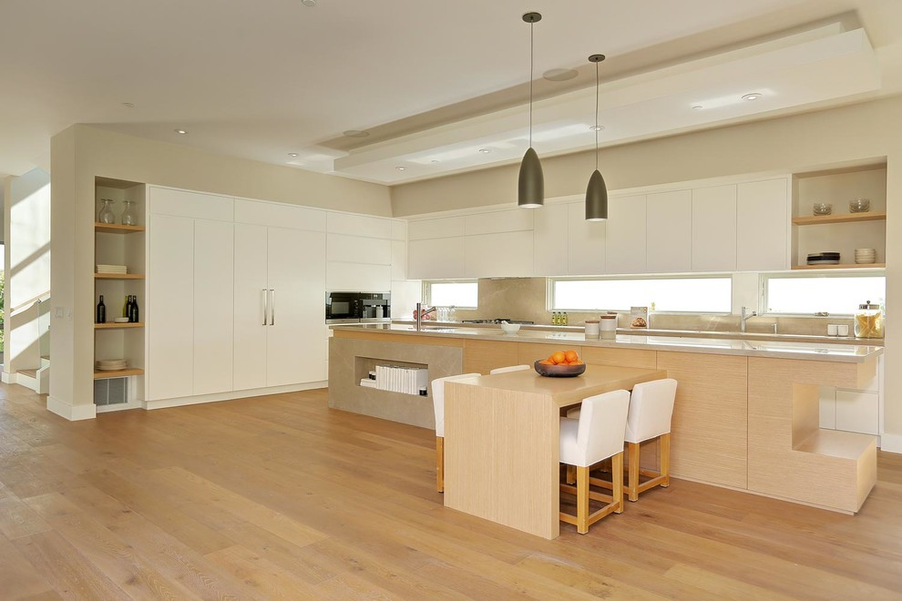 Large minimalist l-shaped medium tone wood floor eat-in kitchen photo in Los Angeles with an undermount sink, flat-panel cabinets, white cabinets, marble countertops, gray backsplash, stone slab backsplash, stainless steel appliances and an island