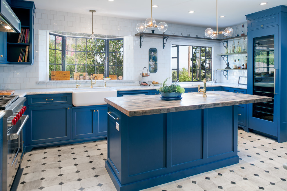 Large tuscan u-shaped concrete floor and multicolored floor kitchen photo in Los Angeles with a farmhouse sink, recessed-panel cabinets, blue cabinets, marble countertops, white backsplash, subway tile backsplash, paneled appliances and an island
