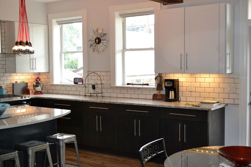 Modelo de cocina urbana, grande, con fregadero bajoencimera, salpicadero de azulejos tipo metro, electrodomésticos de acero inoxidable, suelo de baldosas de porcelana y una isla