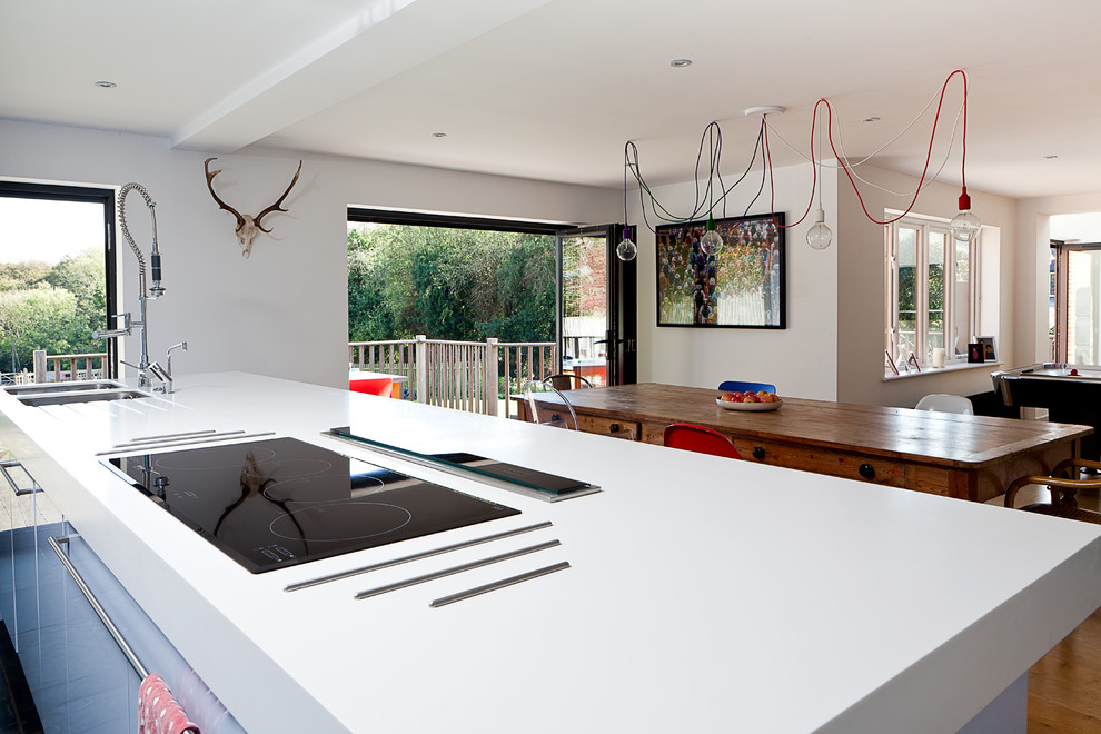 This is an example of a contemporary open plan kitchen in London with a double-bowl sink, flat-panel cabinets and white cabinets.