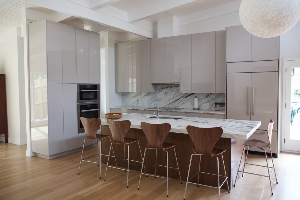 Mid-sized trendy l-shaped light wood floor and brown floor open concept kitchen photo in Atlanta with an undermount sink, flat-panel cabinets, gray cabinets, paneled appliances, an island, marble countertops, white backsplash and marble backsplash