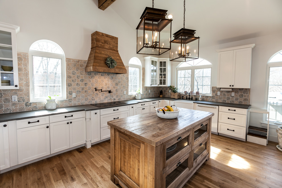 Example of a farmhouse medium tone wood floor kitchen design in St Louis with granite countertops, ceramic backsplash, an island and black countertops