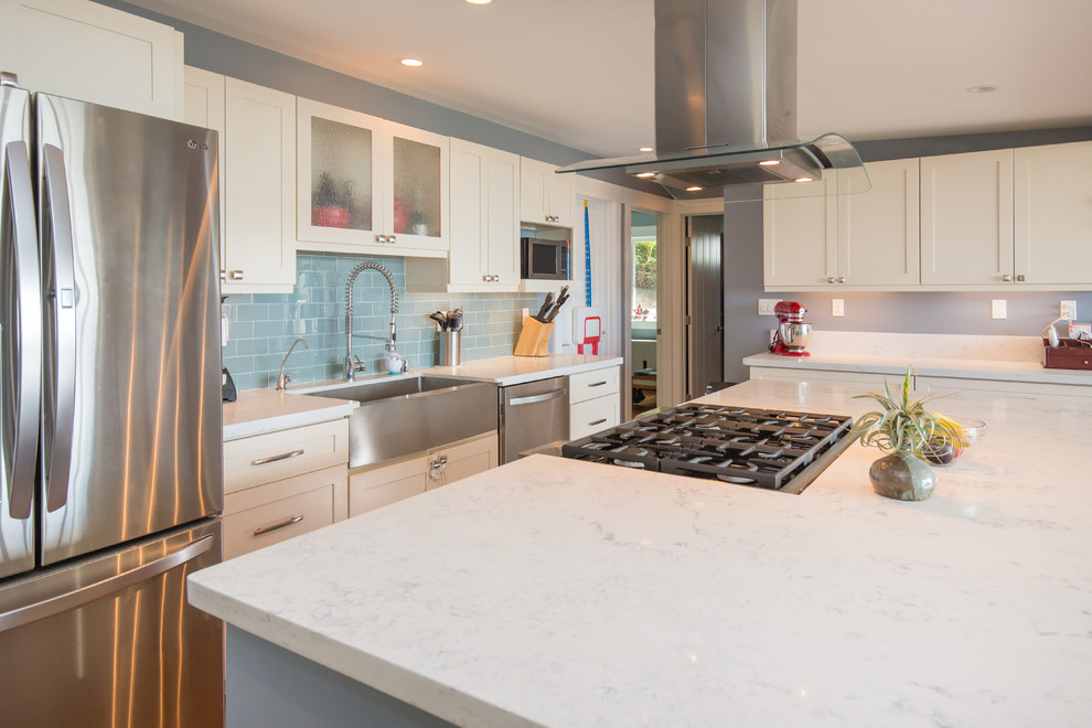 Example of a large transitional l-shaped light wood floor open concept kitchen design in Hawaii with a farmhouse sink, shaker cabinets, white cabinets, quartz countertops, blue backsplash, subway tile backsplash, stainless steel appliances and an island