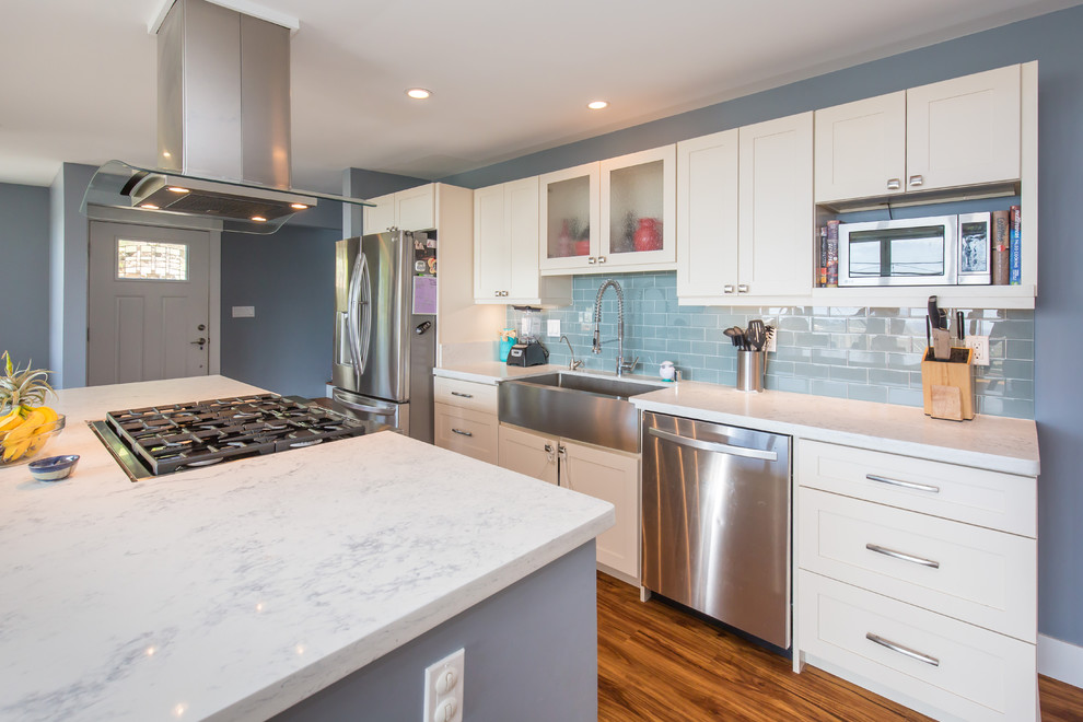 Open concept kitchen - large transitional l-shaped light wood floor open concept kitchen idea in Hawaii with a farmhouse sink, shaker cabinets, white cabinets, quartz countertops, blue backsplash, subway tile backsplash, stainless steel appliances and an island