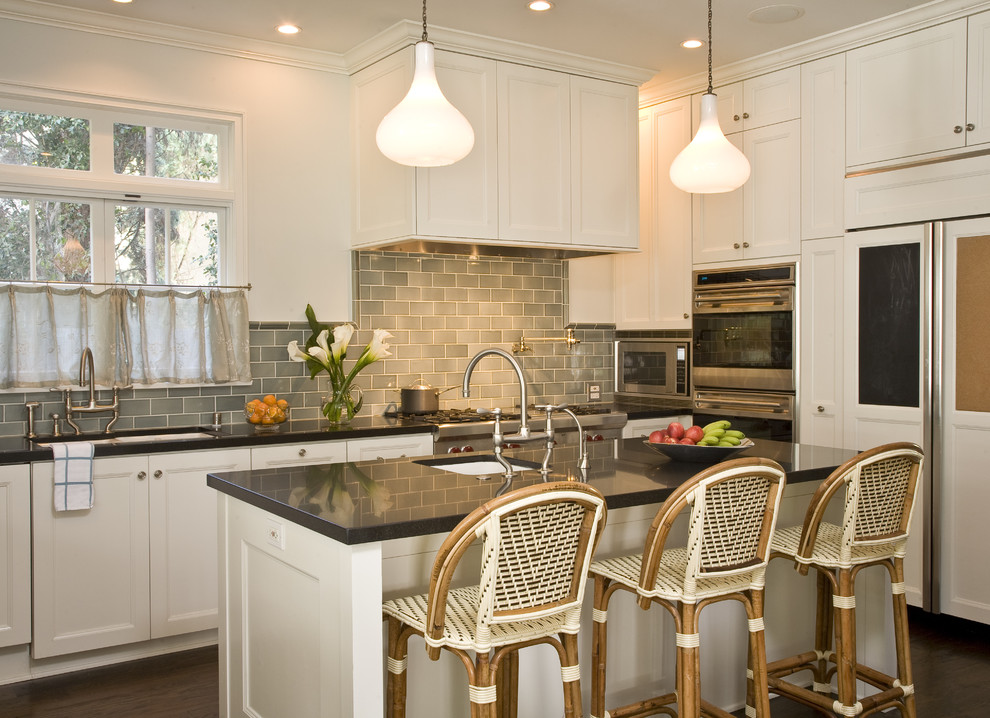 Kitchen - traditional u-shaped kitchen idea in Los Angeles with paneled appliances, an undermount sink, recessed-panel cabinets, white cabinets, quartz countertops, gray backsplash and subway tile backsplash
