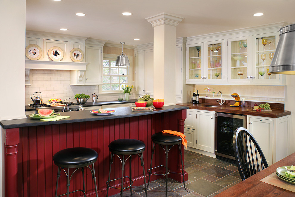 Elegant eat-in kitchen photo in Newark with stainless steel appliances, an undermount sink, wood countertops, glass-front cabinets and white cabinets