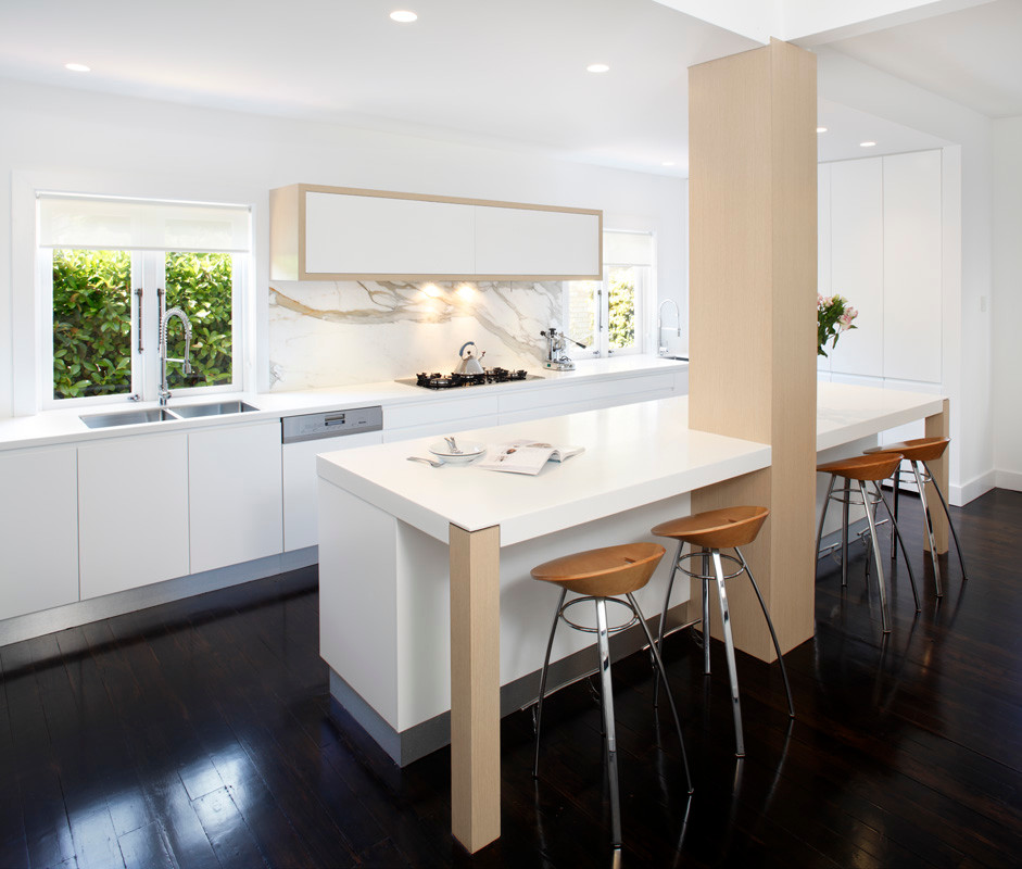 Minimalist single-wall eat-in kitchen photo in Sydney with a drop-in sink, flat-panel cabinets, white cabinets, solid surface countertops, stone slab backsplash and stainless steel appliances