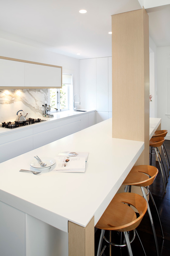 Example of a minimalist single-wall eat-in kitchen design in Sydney with a drop-in sink, flat-panel cabinets, white cabinets, solid surface countertops, stone slab backsplash and stainless steel appliances