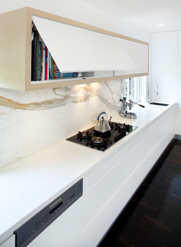 Inspiration for a modern single-wall eat-in kitchen remodel in Sydney with a drop-in sink, flat-panel cabinets, white cabinets, solid surface countertops, stainless steel appliances, white backsplash and marble backsplash