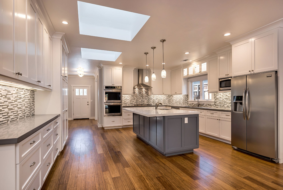 Open concept kitchen - mid-sized craftsman l-shaped medium tone wood floor open concept kitchen idea in San Francisco with an undermount sink, shaker cabinets, white cabinets, quartz countertops, multicolored backsplash, glass tile backsplash, stainless steel appliances and an island
