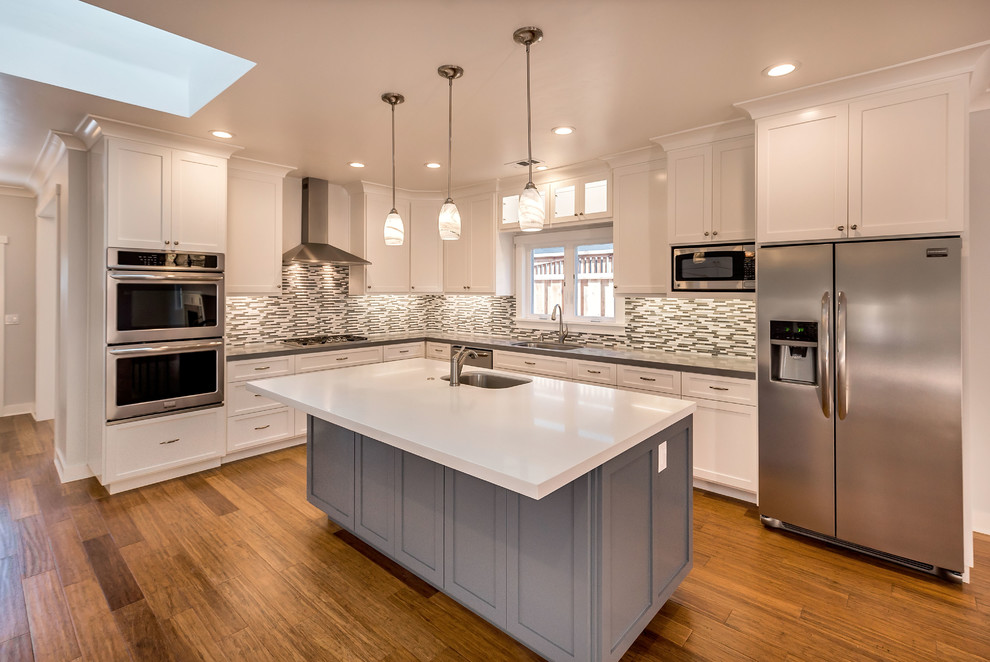 Mid-sized arts and crafts l-shaped medium tone wood floor open concept kitchen photo in San Francisco with an undermount sink, shaker cabinets, white cabinets, quartz countertops, multicolored backsplash, glass tile backsplash, stainless steel appliances and an island