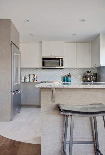 Kitchen - contemporary u-shaped porcelain floor kitchen idea in Calgary with an undermount sink, flat-panel cabinets, gray cabinets, granite countertops, gray backsplash, mosaic tile backsplash, stainless steel appliances and a peninsula
