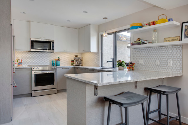 Trendy u-shaped porcelain floor eat-in kitchen photo in Calgary with an undermount sink, flat-panel cabinets, gray cabinets, granite countertops, gray backsplash, mosaic tile backsplash, stainless steel appliances and a peninsula