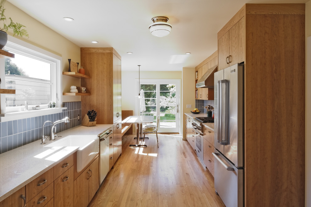 Transitional galley enclosed kitchen photo in Portland with a farmhouse sink, stainless steel appliances, flat-panel cabinets, medium tone wood cabinets, recycled glass countertops, blue backsplash and ceramic backsplash