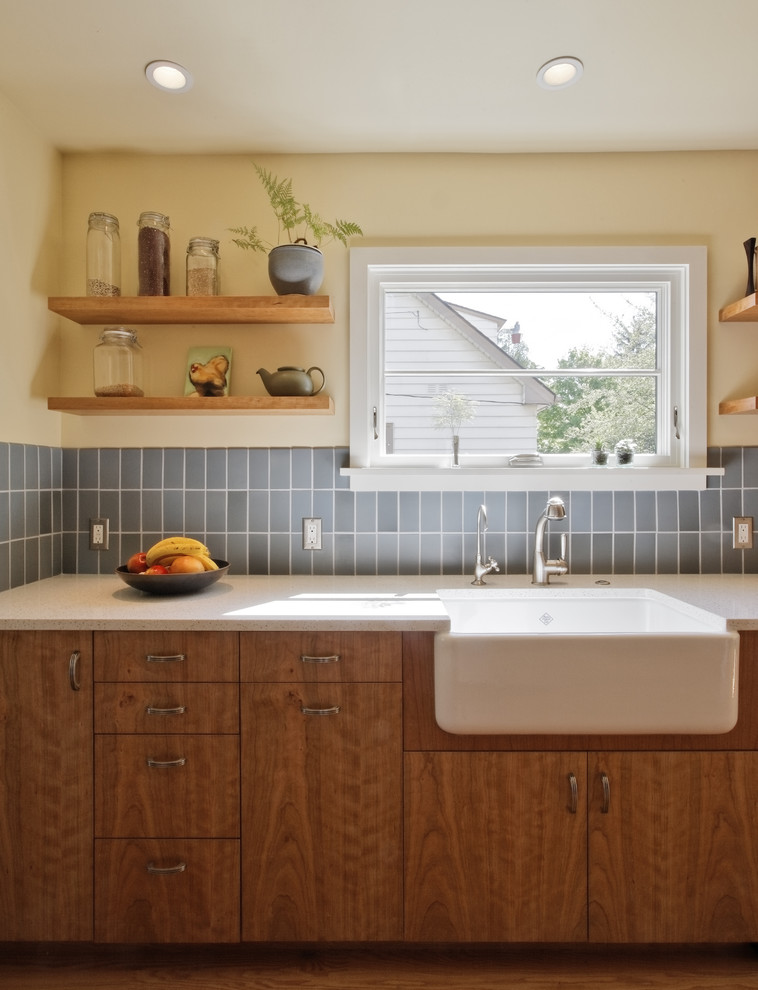 Eat-in kitchen - transitional galley eat-in kitchen idea in Portland with a farmhouse sink, blue backsplash, flat-panel cabinets, medium tone wood cabinets, recycled glass countertops, ceramic backsplash and stainless steel appliances