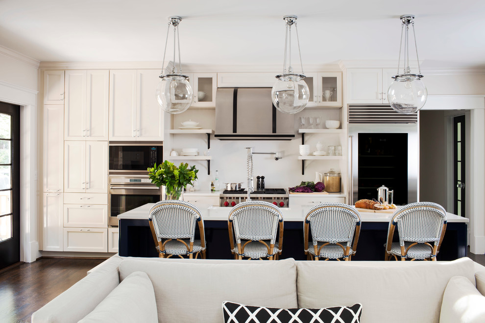 Open concept kitchen - transitional galley dark wood floor open concept kitchen idea in Atlanta with a farmhouse sink, recessed-panel cabinets, solid surface countertops, white backsplash, stainless steel appliances and an island