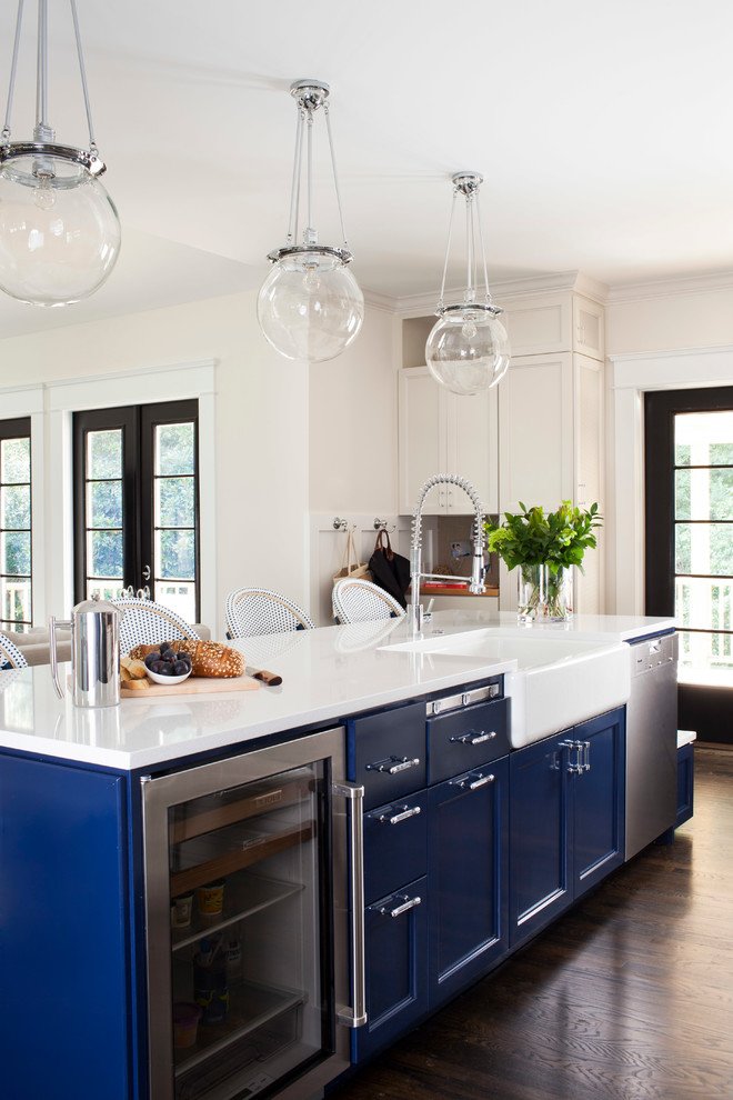 Inspiration for a mid-sized transitional galley dark wood floor open concept kitchen remodel in Atlanta with a farmhouse sink, recessed-panel cabinets, blue cabinets, solid surface countertops, stainless steel appliances and an island