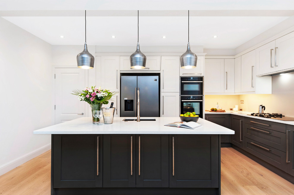 Large transitional l-shaped light wood floor and beige floor kitchen photo in London with shaker cabinets, black cabinets, quartzite countertops, an island, white countertops, an undermount sink and stainless steel appliances