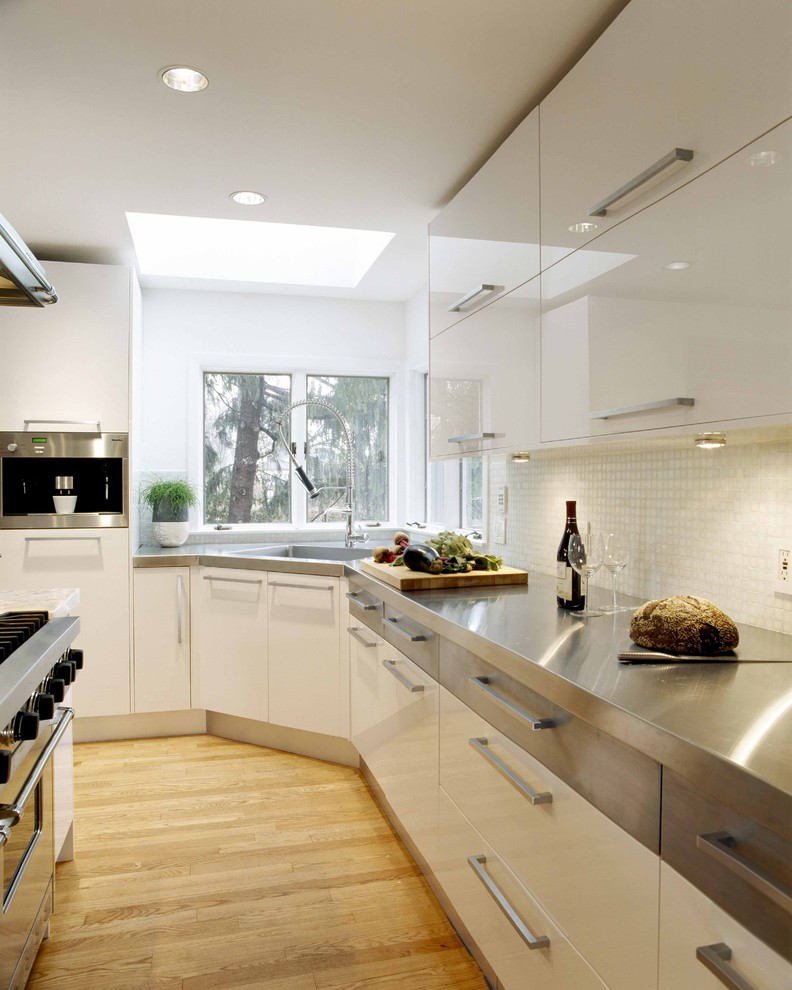 Example of a trendy kitchen design in Boston with stainless steel appliances, concrete countertops, an integrated sink, flat-panel cabinets, white cabinets, white backsplash and mosaic tile backsplash