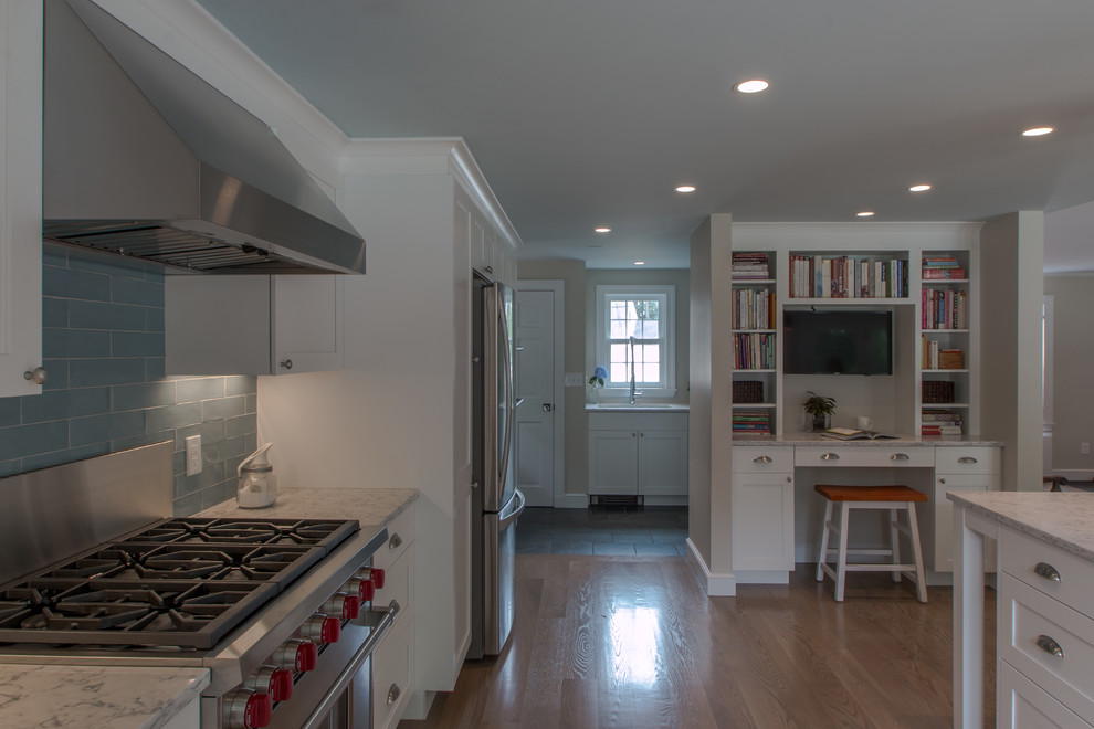 Kitchen - traditional u-shaped medium tone wood floor kitchen idea in Boston with a farmhouse sink, recessed-panel cabinets, white cabinets, quartz countertops, blue backsplash, glass tile backsplash, stainless steel appliances and an island