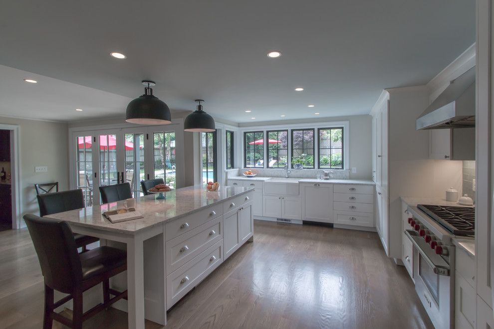 Inspiration for a timeless u-shaped medium tone wood floor kitchen remodel in Boston with a farmhouse sink, recessed-panel cabinets, white cabinets, quartz countertops, blue backsplash, glass tile backsplash, stainless steel appliances and an island