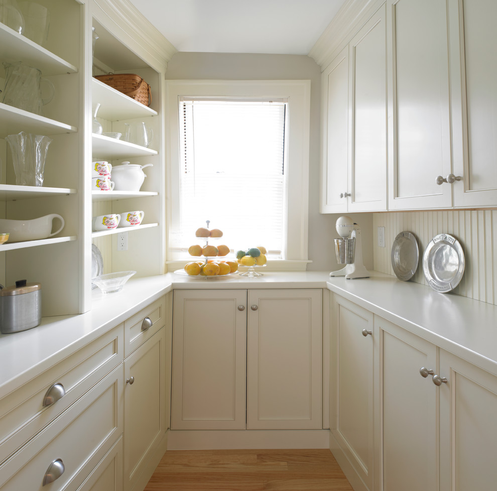 Inspiration for a large timeless u-shaped medium tone wood floor kitchen pantry remodel in Boston with recessed-panel cabinets, white cabinets, solid surface countertops, white backsplash, wood backsplash and no island