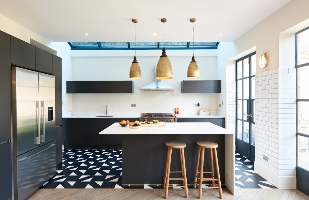 Example of a trendy l-shaped multicolored floor kitchen design in London with an undermount sink, flat-panel cabinets, white backsplash, white appliances and an island