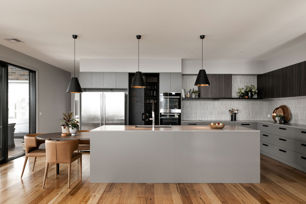 Inspiration for a large contemporary l-shaped brown floor kitchen remodel in Melbourne with an undermount sink, flat-panel cabinets, gray cabinets, gray backsplash, an island and gray countertops