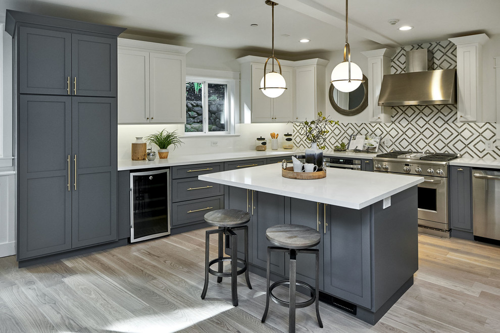 Kitchen - transitional l-shaped light wood floor and beige floor kitchen idea in San Francisco with shaker cabinets, gray cabinets, stainless steel appliances, an island and white countertops