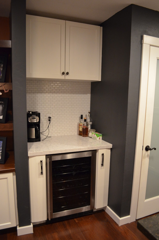 Example of a trendy dark wood floor kitchen design in Sacramento with recessed-panel cabinets, white cabinets, white backsplash and stainless steel appliances