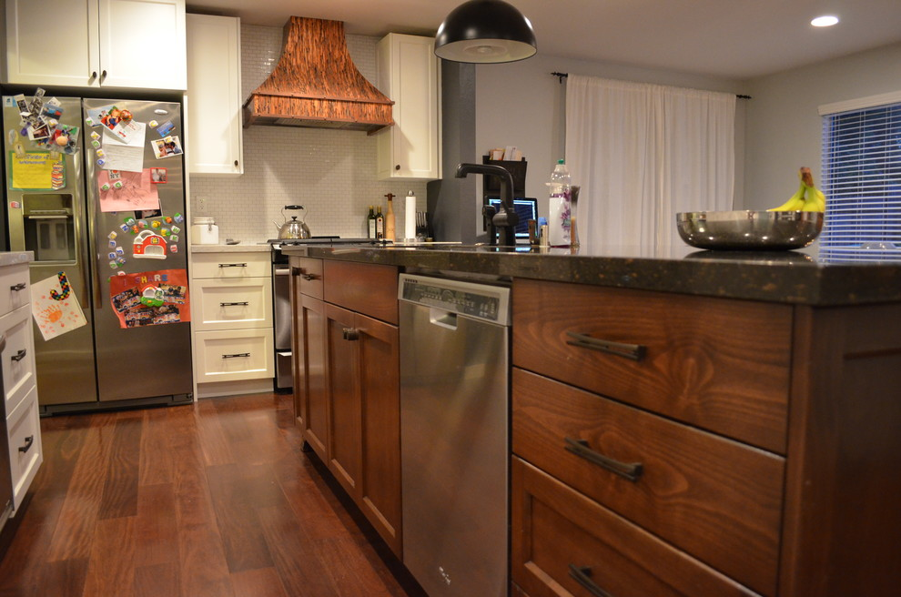 Example of a trendy dark wood floor kitchen design in Sacramento with an undermount sink, recessed-panel cabinets, dark wood cabinets, stainless steel appliances and an island
