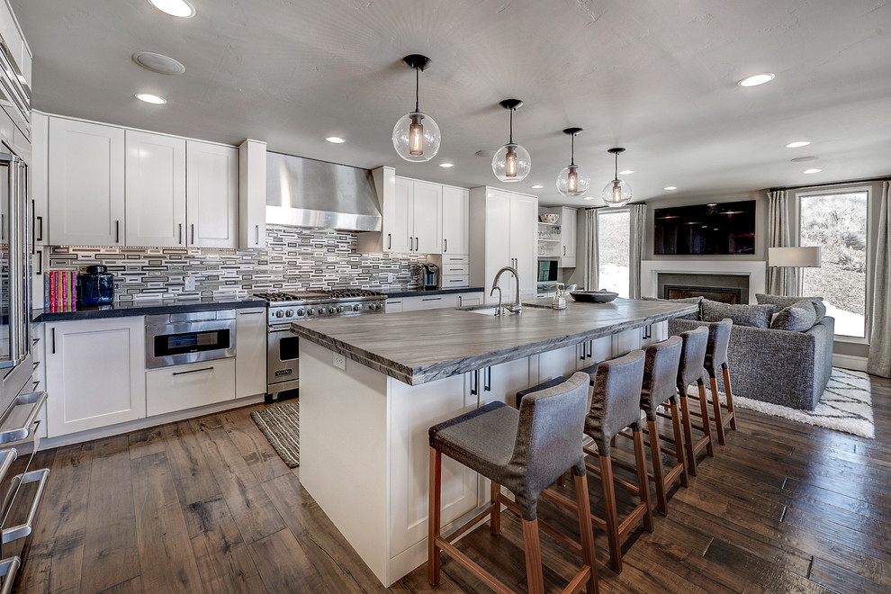 Transitional galley medium tone wood floor open concept kitchen photo in Denver with an undermount sink, shaker cabinets, white cabinets, stainless steel appliances and an island