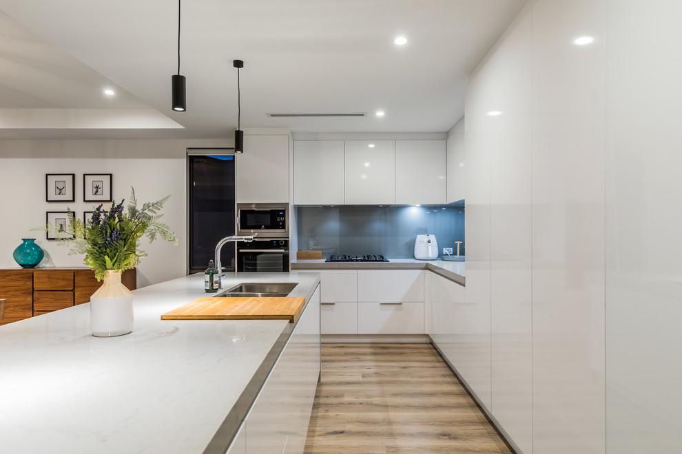 パースのコンテンポラリースタイルのおしゃれなキッチン (アンダーカウンターシンク、フラットパネル扉のキャビネット、白いキャビネット、青いキッチンパネル、ガラス板のキッチンパネル、無垢フローリング、茶色い床、グレーのキッチンカウンター) の写真