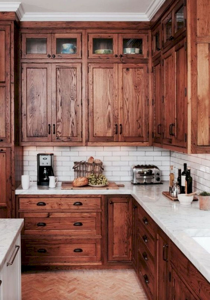 Example of a large classic l-shaped brown floor and ceramic tile eat-in kitchen design in Columbus with shaker cabinets, white backsplash, stainless steel appliances, an island, white countertops, an undermount sink, medium tone wood cabinets, marble countertops and subway tile backsplash