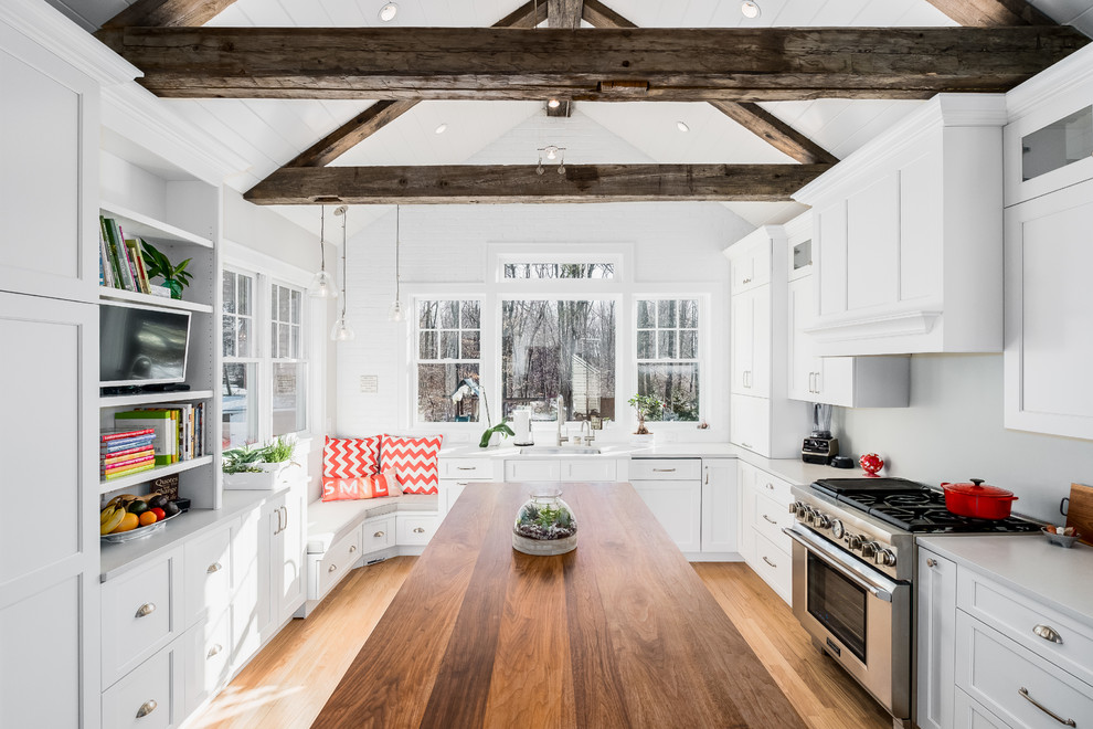 Example of a mid-sized cottage l-shaped light wood floor eat-in kitchen design in New York with an undermount sink, white cabinets, quartz countertops, stainless steel appliances, an island, beaded inset cabinets and gray backsplash