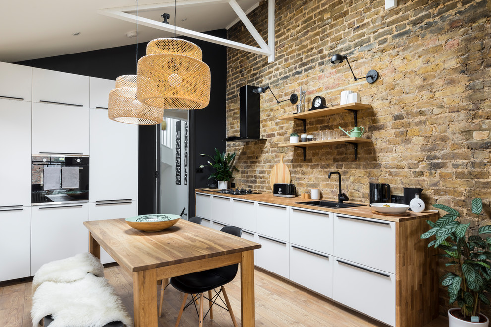 Kitchen - industrial medium tone wood floor and brown floor kitchen idea in London with a drop-in sink, flat-panel cabinets, white cabinets, wood countertops, stainless steel appliances and an island