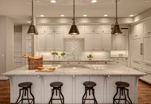 Large white kitchen with pewter pendant lights and four backless swivel bar stools in pewter
