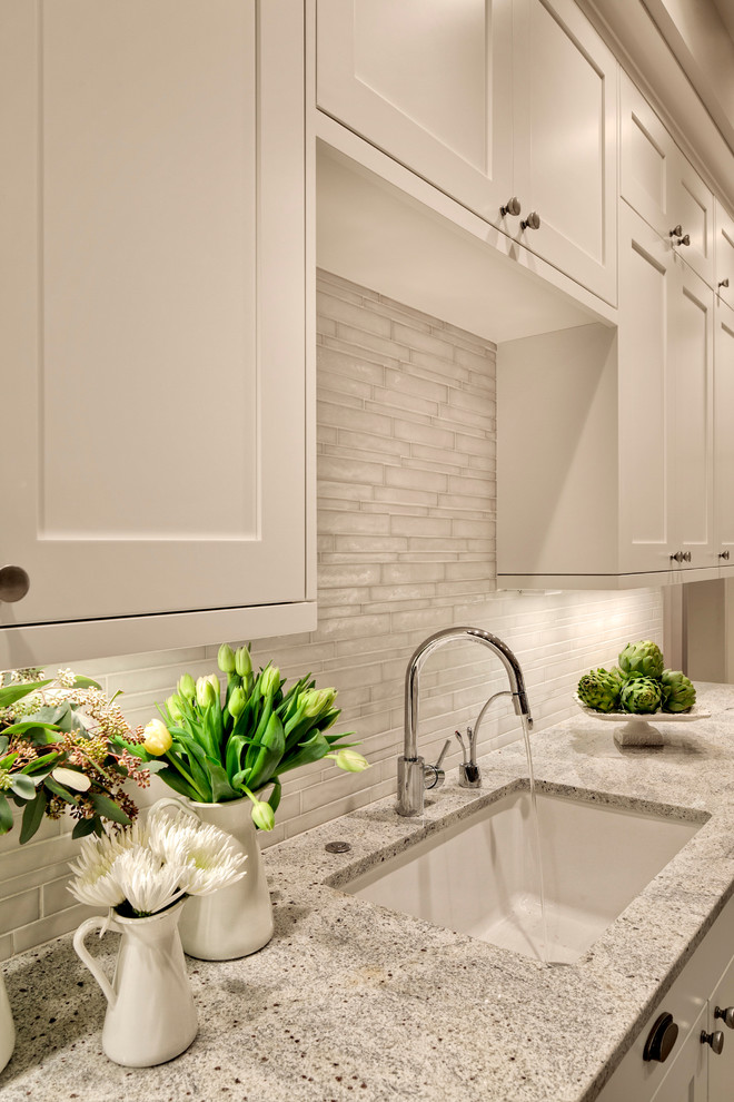 Kitchen pantry - huge contemporary kitchen pantry idea in Seattle with an undermount sink, shaker cabinets, white cabinets, granite countertops, white backsplash, glass tile backsplash and an island