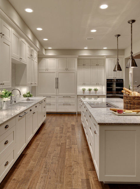 Example of a huge transitional medium tone wood floor kitchen design in Seattle with an undermount sink, shaker cabinets, white backsplash, paneled appliances, granite countertops, glass tile backsplash, an island, white cabinets and gray countertops