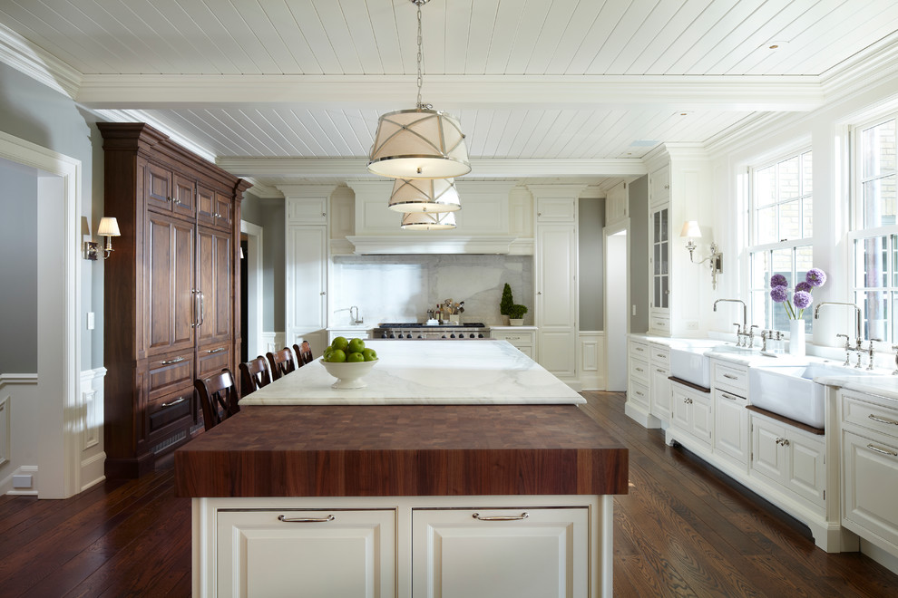 Example of a classic kitchen design in Minneapolis with a farmhouse sink, raised-panel cabinets, white cabinets, marble countertops, white backsplash, stone slab backsplash and paneled appliances