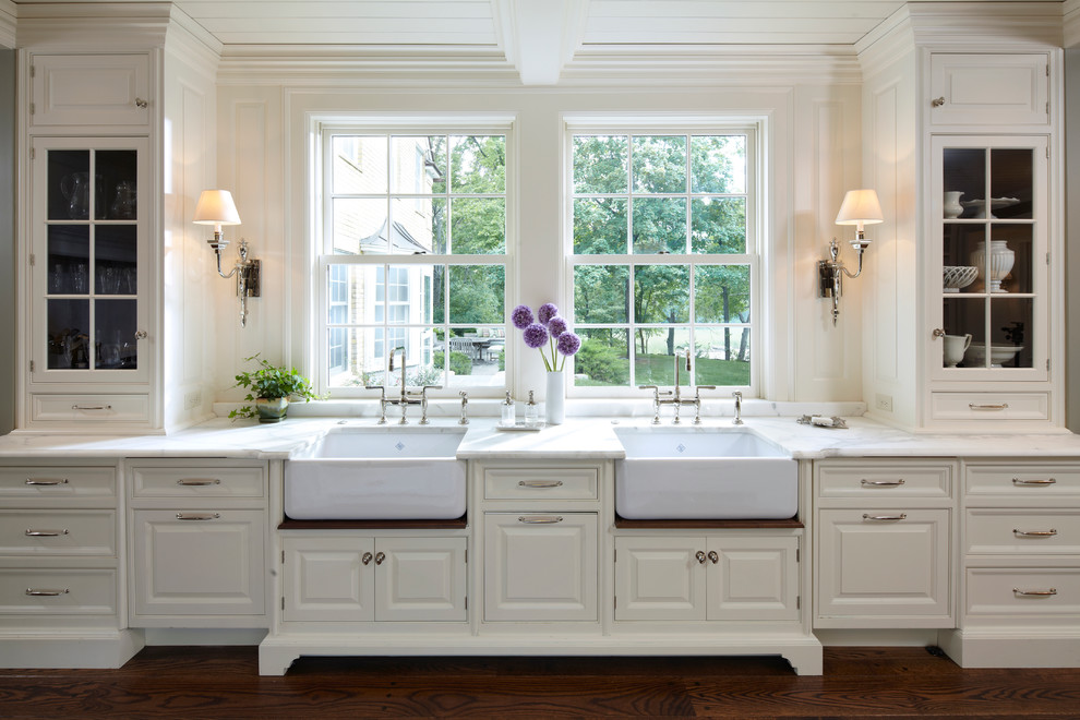 Elegant kitchen photo in Minneapolis with a farmhouse sink, glass-front cabinets, white cabinets and marble countertops