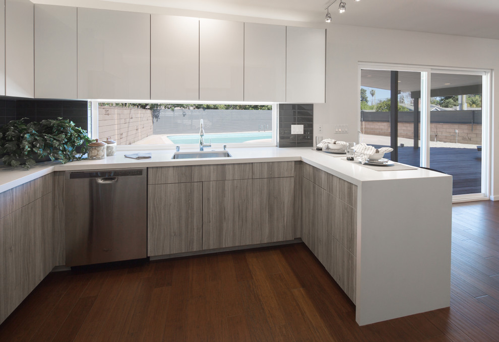 Example of a mid-sized trendy u-shaped dark wood floor and brown floor eat-in kitchen design in Los Angeles with an undermount sink, flat-panel cabinets, white cabinets, quartz countertops, gray backsplash, porcelain backsplash, stainless steel appliances and a peninsula